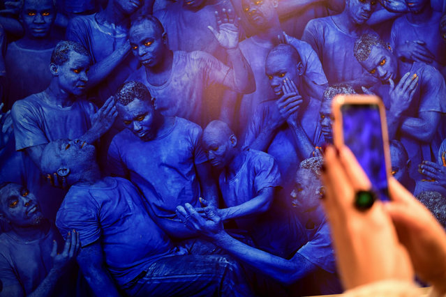 """A visitor takes pictures with a smartphone of an artwork entitled """"Blue Europe, 2015"""" by Chinese artist Liu Bolin, on display during the exhibition """"Visible Invisible"""" at the Mudec Museum in Milan on May 14, 2019. Liu Bolin known as """"the invisible man"""" for his photographic self-portraits, focused on a body-painting blending with the surrounding area. (Photo by Miguel Medina/AFP Photo)"""