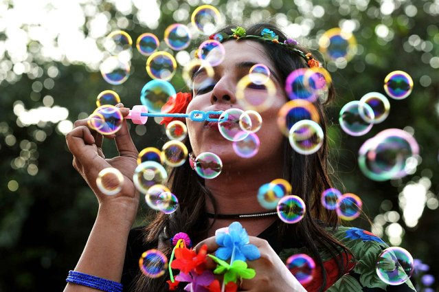 An Indian transgender activist blows bubbles during the annual Bengaluru Pride March in Bangalore on November 23, 2014. The annual march is aimed at ending violence and opression based gender identity and sexual orientation. (Photo by Manjunath Kiran/AFP Photo)