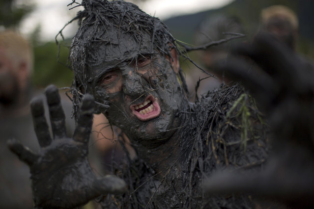 """A mud-covered partygoer strikes a pose during the traditional """"Bloco da Lama"""" or """"Mud Street"""" carnival party, in Paraty, Brazil, Saturday, February 25, 2017. (Photo by Mauro Pimentel/AP Photo)"""