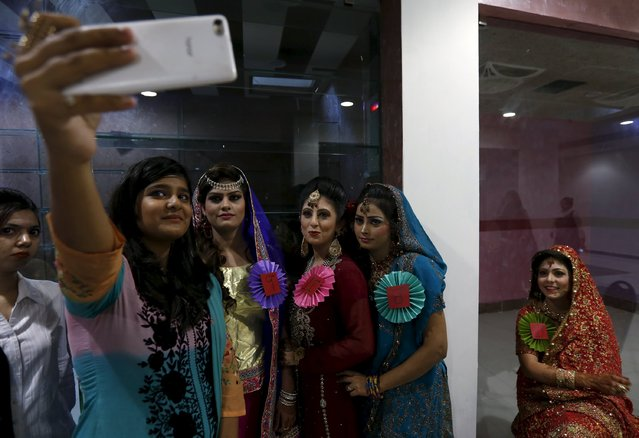 A girl takes a selfie with models backstage after a self grooming bridal beauty workshop at a local mall in Karachi, Pakistan, March 22, 2016. (Photo by Akhtar Soomro/Reuters)