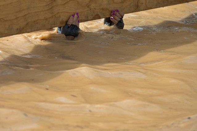 A participant in a mud pool ducks under low barrier while taking part in the Mud Day athletic event in Toledo, Spain, Saturday, May 23, 2015. Thousands of runners  are competing the challenge in a mud circuit of approximately 13 kilometers (8 miles) with 22 obstacles. (Photo by Paul White/AP Photo)