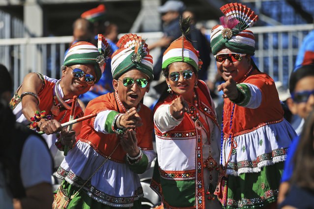 Indian cricket fans, dressed in the colors of their national flag, cheer before the start of the Cricket World Cup match between India and West Indies at Old Trafford in Manchester, England, Thursday, June 27, 2019. (Photo by Jon Super/AP Photo)