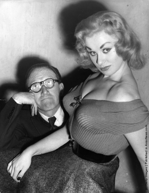 Glamour model and actress Sabrina seated on the knee of Arthur Askey, 1955
