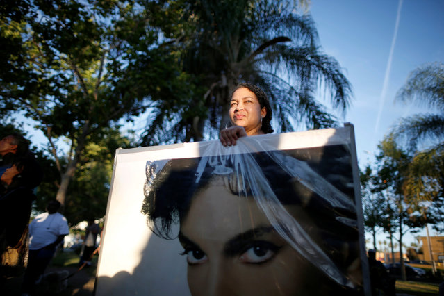 Jennifer Matthews, 52, holds a poster of Prince at a vigil to celebrate the life and music of deceased musician Prince in Los Angeles, California, U.S., April 21, 2016. (Photo by Lucy Nicholson/Reuters)