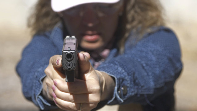 In this Saturday, June 29, 2019, photo, Cindy Bullock, Timpanogos Academy secretary, participates in shooting drills at the Utah County Sheriff's Office shooting range during the teacher's academy training, in Spanish Fork Canyon, Utah. About 30 teachers in Utah are spending their summer learning how to stuff wounds and shoot guns as part of a training held by police to prepare educators for an active shooter scenario in their schools. (Photo by Rick Bowmer/AP Photo)