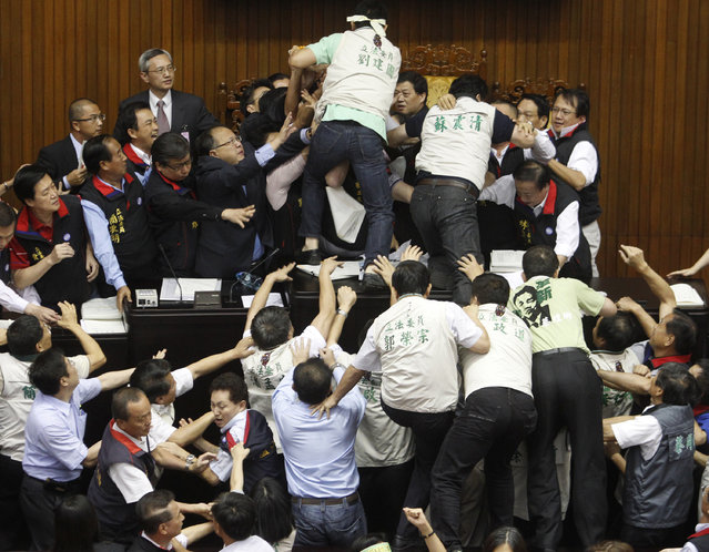 Opposition Democratic Progressive Party (DPP) legislators scuffle with ruling Nationalist Party (KMT) legislators (top) at the Legislative Yuan in Taipei July 8, 2010. (Photo by Nicky Loh/Reuters)