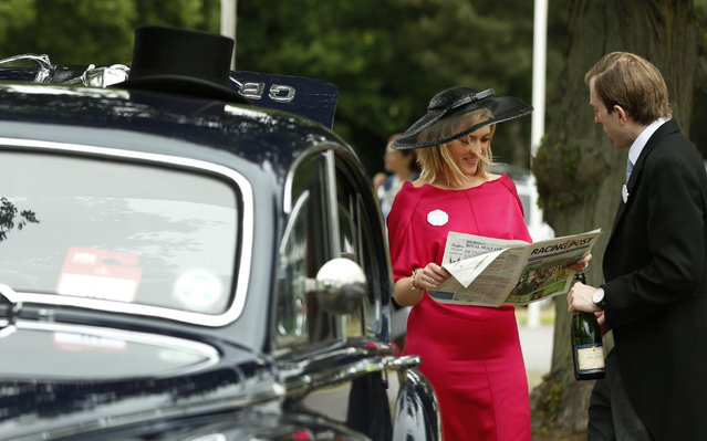 William Beddall and his wife Milly read a racing paper in the car park on the second day of  Royal Ascot horse racing meet at Ascot, England, Wednesday, June 17, 2015. Royal Ascot is the annual five day horse race meeting that Britain's Queen Elizabeth II attends every day of the event.(AP Photo/Alastair Grant)