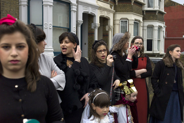 Jewish women watch as men dance down the street during the annual Jewish holiday of Purim on March 12, 2017 in London, England. (Photo by Dan Kitwood/Getty Images)
