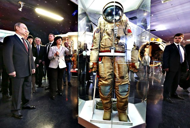 Russia's President Vladimir Putin (L) listens to explanations and looks at an exhibit as he visits the Cosmonautics Memorial Museum in Moscow, Russia, 11 April 2014. On Saturday, Russia celebrates Cosmonautics day which marks Yuri Gagarin's pioneering flight into space. (Photo by Sergei Karpukhin/EPA)