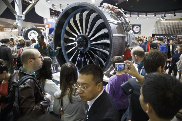 Visitors look at a LEAP engine (Leading Edge Aviation Propulsion) by CFM international, during the closing day of the Paris Air Show in Le Bourget, north of Paris, Sunday,  June 21, 2015. Some 300,000 aviation professionals and spectators are expected at this week's Paris Air Show, coming from around the world to make business deals and see dramatic displays of aeronautic prowess and the latest air and space technology. (AP Photo/Michel Euler)