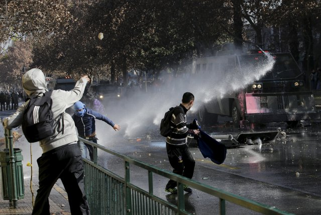 A police vehicle aims a jet of water to disperse students demonstrating to demand changes in the education system, in Santiago, Chile June 25, 2015. (Photo by Henry Romero/Reuters)