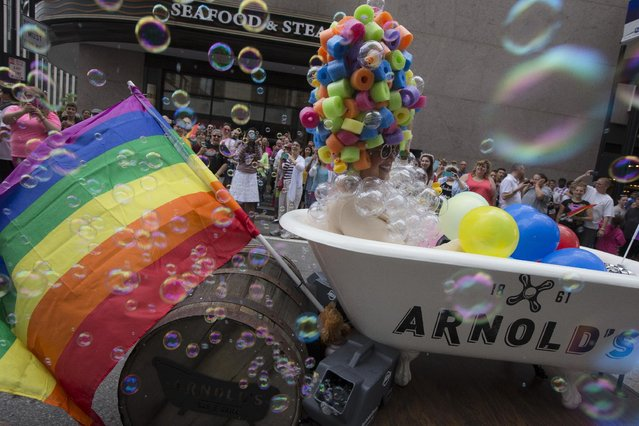 Pam Kravetz rides her bubble-bath through downtown Cincinnati during the Cincinnati Pride parade, Saturday, June 27, 2015. On Friday, the U.S. Supreme Court ruled that same-s*x couples have the right to marry nationwide. (Photo by John Minchillo/AP Photo)