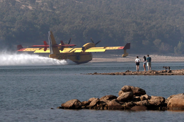 A flying boat takes water from La Pinilla dam in Pinilla del Valle, Madrid, Spain, 05 August 2019, to extinguish the forest fires that broke out in the village of Mirasierra and the nearby San Ildefonso-La Granja. Both forest fires are threating Guadarrama Natural Reserve. (Photo by EPA/EFE/Mariscal)