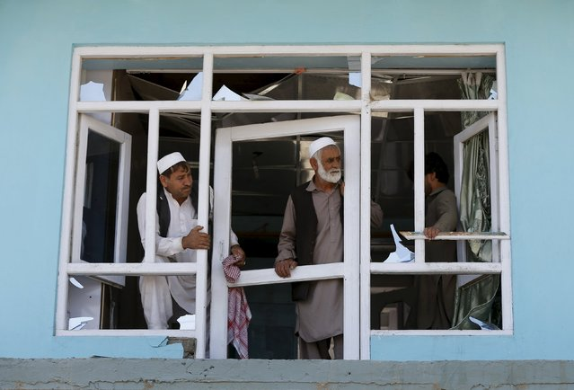Afghan men look out from their window house at the site of a suicide bomb attack in Kabul, Afghanistan, June 30, 2015. (Photo by Omar Sobhani/Reuters)