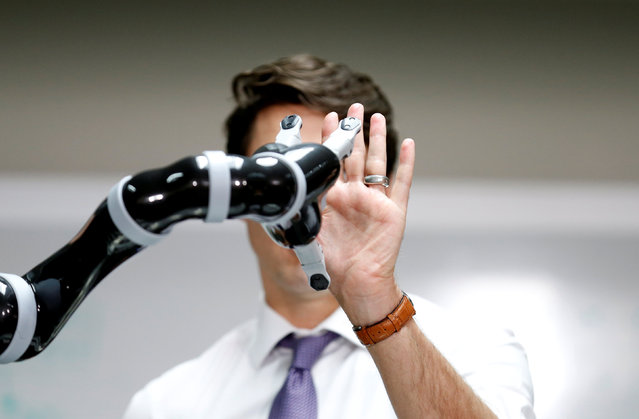 Canadian Prime Minister Justin Trudeau high fives a robotic arm as he takes part in a robotics demonstration at Kinova Robotics in Boisbriand, Quebec, Canada March 24, 2017. (Photo by Christinne Muschi/Reuters)