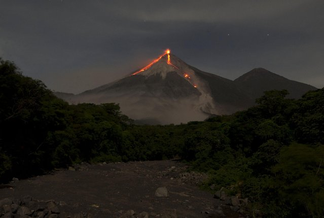 In this image taken with a long exposure, the Volcan de Fuego, or Volcano of Fire, spews hot molten lava from its crater in San Juan Alotenango, Guatemala, Wednesday, July 1, 2015. The Guatemalan emergency agency CONRED raised the alert level in the area after the volcano restarted its activity on early Wednesday. (Photo by Moises Castillo/AP Photo)