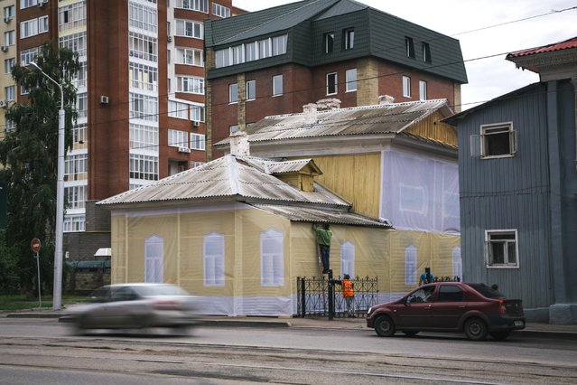 In this photo taken on Sunday, July  5, 2015, municipal workers cover an old house to give it a  better look, in downtown Ufa, Russia. (Photo by Vadim Braydov/AP Photo)