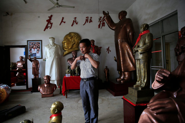 Chinese sculptor Tian Yongjun adjusts his collar as he prepares to leave his workshop of Mao Zedong statues in Shaoshan, Hunan Province in central China, 29 April 2016. Tian has been a sculptor making Mao statues for over 20 years. (Photo by How Hwee Young/EPA)