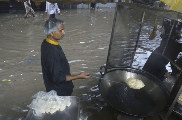 A vendor prepares food as the street is flooded after a heavy rainfall in Lahore, Pakistan, Thursday, July 25, 2019. Pakistani authorities issued a warning of heavy rains and flooding during a monsoon. (Photo by K.M. Chaudary/AP Photo)