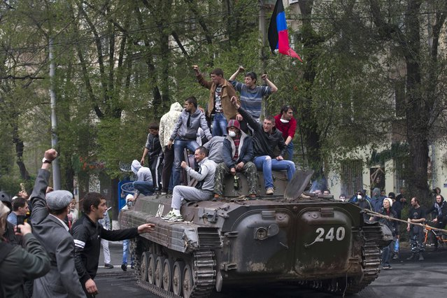 People greet pro-Russian activists atop of a government forces armored personal carrier captured from the enemy in fighting  in Mariupol, eastern Ukraine, Friday, May 9, 2014. Fighting exploded Friday in Mariupol, a city of 500,000 on the Sea of Azov that is on the main road between Russia proper and Crimea. The fighting between government forces and insurgents in Mariupol has left several people dead. (Photo by Alexander Zemlianichenko/AP Photo)