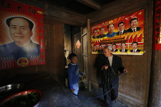 Xie Guobiao (L), 11, is tied up by a rope as he walks with his grandfather in front of posters depicting the late Communist Party of China Chairman Mao Zedong and other former and current Chinese politicians at his home in Daohui village of Lishui, Zhejiang province May 8, 2014. (Photo by William Hong/Reuters)