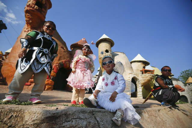 """(L-R) """"Dwarf Empire"""" cast members Han Gui Lan, 23-year-old Liu Jin Jin, 19-year-old Han Zhen Yan and Yin Zheng Xiong pose in their costumes backstage in front of the fairy tale-like village at the Dwarf Empire theme park outside Kunming, China's Yunnan province, 03 April 2013. (Photo by Diego Azubel/EPA)"""