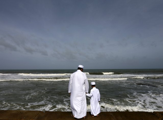A Sri Lankan Muslim father and son stand in front of the sea during morning prayers of Eid al-Fitr celebrations marking the end of Ramadan, the holiest month in the Islamic calendar in Colombo, Sri Lanka July 18, 2015. (Photo by Dinuka Liyanawatte/Reuters)