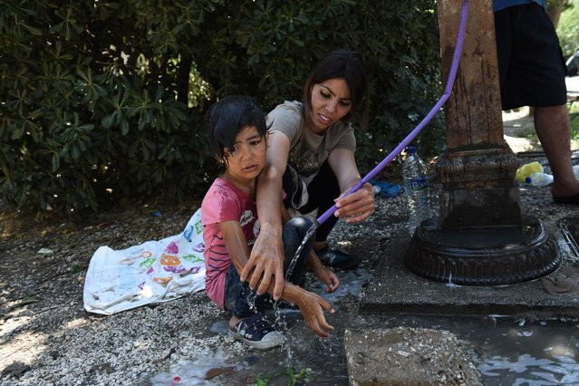 Afghan refugees wash at a tap in the Pedion tou Areos park in central Athens, on Friday, July 24, 2015. (Photo by Giannis Papanikos/AP Photo)