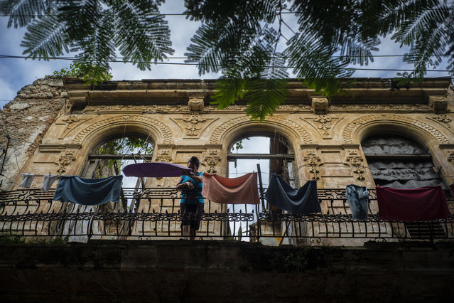 In this November 10, 2019 photo, a woman pulls towels off the line after they dried on the balcony of an old home, missing part of its roof, in Havana, Cuba. (Photo by Ramon Espinosa/AP Photo)