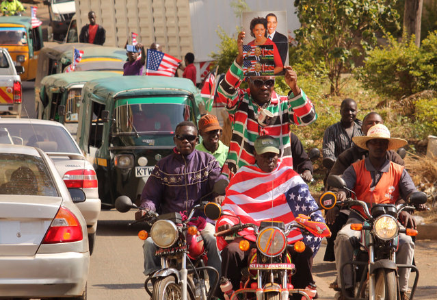 "People on motor bikes celebrate American President Barack Obama's visit to Kenya by holding up a photo, center top, of the president and First Lady Michelle Obama in Kisumu, Kenya, Saturday, July 25, 2015.  President Barack Obama heralded Africa as a continent ""on the move"" Saturday as he opened a U.S.-sponsored business summit in Kenya, the East African nation where he has deep family ties. (Photo by AP Photo)"