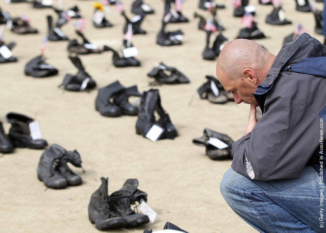 A man pauses as he looks at rows of combat boots that are part of the Eyes Wide Open exhibit in front of San Francisco City Hall