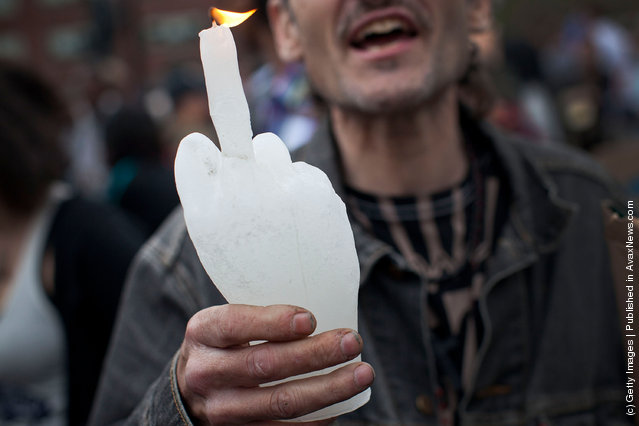 An Occupy Wall Street protester holds up a candle in the shape of a hand giving the middle finger in Union Square at the end of a march from Zuccotti Park