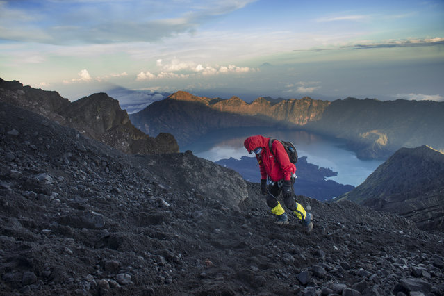 """""""Chasing The Sun"""". A trekker on the way to the summit of Mount Rinjani. Mount Rinjani is second highest active volcano in Indonesia, located on the island of Lombok. On the top of the volcano is a caldera that filled partially by crater lake, it's known as Segara Anak. Sasak tribe believe both the lake and the mount are sacred. Photo location: Mount Rinjani, Lombok, Indonesia. (Photo and caption by Lidya Ally/National Geographic Photo Contest)"""