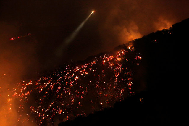 """A helicopter flies over a smoldering hillside as the """"Old Fire"""" burns in Calabasas, California U.S., June 4, 2016. (Photo by Mario Anzuoni/Reuters)"""