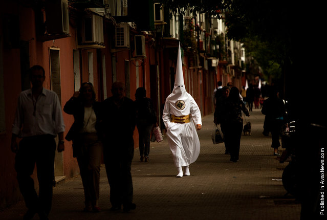 A penitent from the San Gonzalo brotherhood walks toward a church to take part in a procession in Seville, Spain