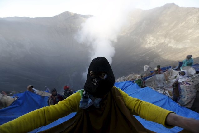 A villager holds onto a portion of a net while standing on the slope of the crater with others while waiting to catch offerings thrown by Hindu worshippers into the crater during the Kasada Festival at Mount Bromo in Probolinggo, Indonesia's East Java province, August 1, 2015. (Photo by Reuters/Beawiharta)