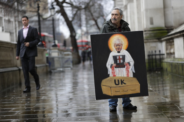 Artist Kaya Mar displays a painting of Britain's Prime Minister Boris Johnson in Westminster in London, Friday, December 20, 2019. British lawmakers are set to hold their first major vote on Prime Minister Boris Johnson's Brexit bill. It is all but certain to be approved by the country's new Conservative-dominated Parliament on Friday. (Photo by Kirsty Wigglesworth/AP Photo)