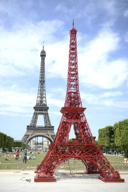 "This picture taken on June 23, 2014 shows a repliqua of the Eiffel Tower, set near the real one, and designed by French designer of outdoor furniture Fermob to mark the Eiffel Tower's 125th anniversary in Paris. The replica is made out of Fermob famous coffee house ""Bistro"" chairs. (Photo by Stephane De Sakutin/AFP Photo)"