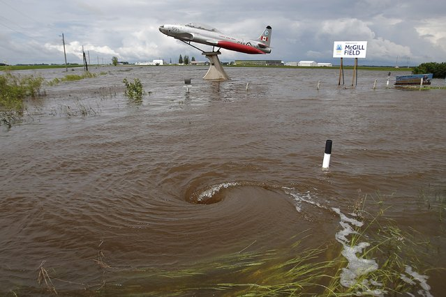 Ditches and culverts are at capacity due to overland flooding in Brandon and surrounding southwest Manitoba, Canada, Monday, June 30, 2014. Southwest Manitoba has seen a large amount of rainfall the past several days. (Photo by John Woods/AP Photo/The  Canadian Press)