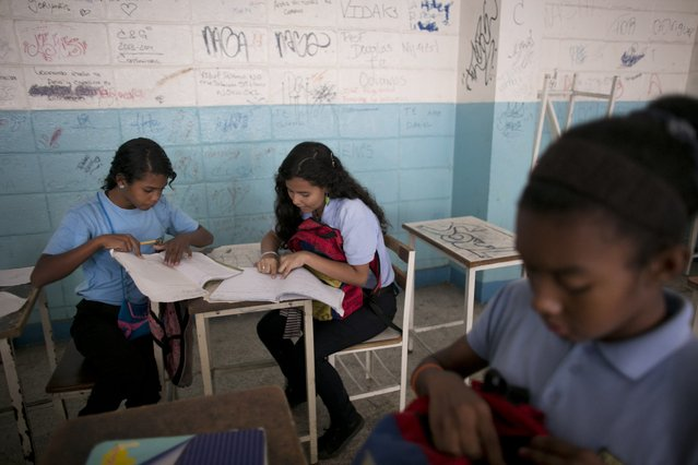 In this June 1, 2016 photo, Maria Arias, center, works with classmates during a math class at her public high school in Caracas, Venezuela. Arias has been held at gunpoint once in school, by a boy so baby-faced she assumed he was a classmate of her 15-year-old sister. Instead, he leveled a gun at her sister's ribs and demanded the girls' flip phones. (Photo by Ariana Cubillos/AP Photo)