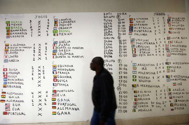 """A man walks in front of a posting on a wall, of the first round World Cup match schedule at a shopping centre in downtown Porto Alegre June 27, 2014. In a project called """"On The Sidelines"""" Reuters photographers share pictures showing their own quirky and creative view of the 2014 World Cup in Brazil. (Photo by Edgard Garrido/Reuters)"""