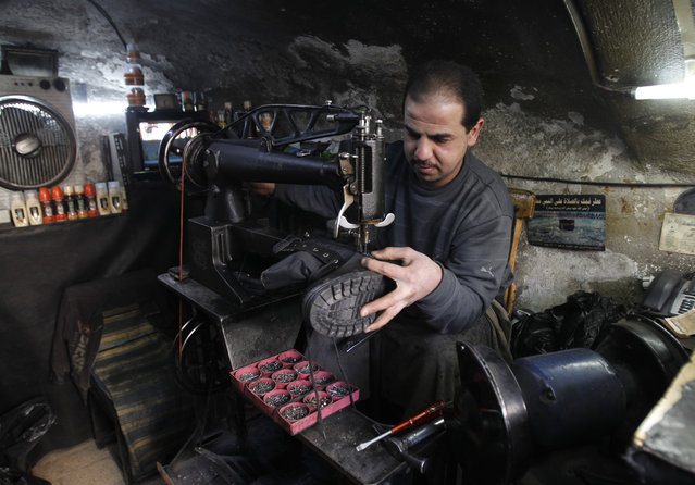 A Syrian cobbler repairs a military boot at his shop in Damascus February 9, 2014. (Photo by Khaled al-Hariri/Reuters)