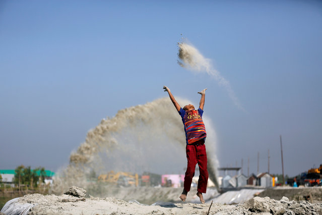A boy plays with sand as his mother works in a nearby restaurant on the outskirt of Dhaka, Bangladesh, November 17, 2016. (Photo by Mohammad Ponir Hossain/Reuters)