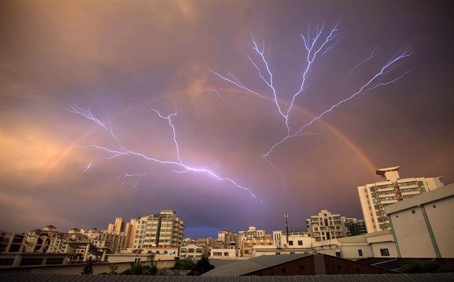 A rainbow is seen in the sky as lightning strikes after a rainstorm in Haikou, Hainan province, China, on May 13, 2012