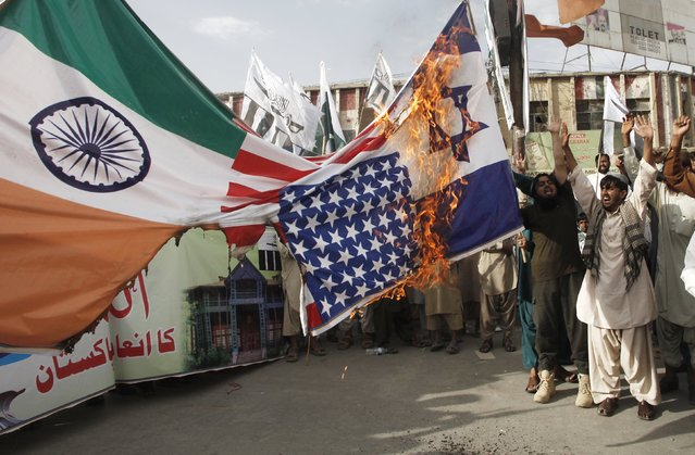Supporters of the Jamaat-ud-Dawa religious party burn Indian, U.S. and Israeli flags at a national day rally during the country's 69th Independence Day in Quetta, Pakistan,  August 14, 2015. (Photo by Naseer Ahmed/Reuters)