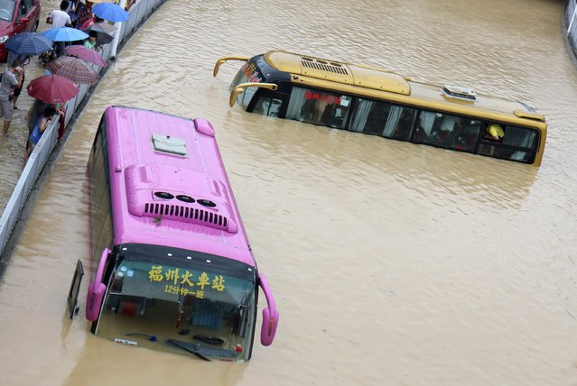 Buses are stranded in a flooded street in Fuzhou, Fujian province, July 24, 2014. Typhoon Matmo hit Taiwan on Wednesday, bringing heavy rain and strong winds, shutting financial markets and schools. It passed the island and headed into China, downgraded from typhoon to tropical storm. (Photo by Reuters/Stringer)