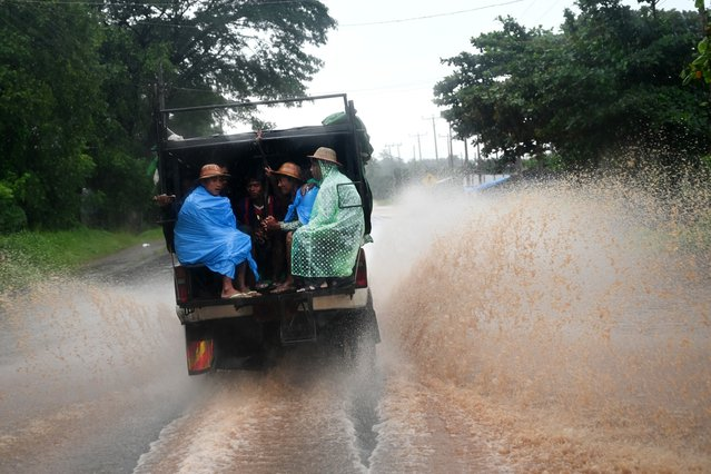 People sit in the back of a truck during heavy rain in Kytehto township, Mon state on August 12, 2019. Myanmar troops and emergency responders scrambled to provide aid in flood-hit parts of the country after rising waters forced residents to flee by boat and a landslide killed at least 52 people. (Photo by Ye Aung Thu/AFP Photo)