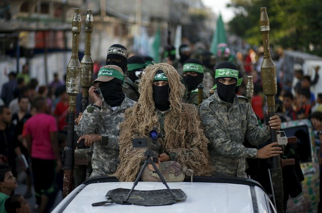 Palestinian Hamas militants take part in a military parade marking the first anniversary of the killing of Hamas's military commanders Mohammed Abu Shammala and Raed al-Attar, in Rafah in the southern Gaza Strip August 21, 2015. Abu Shammala and al-Attar were killed by an Israeli air strike during a 50-day war between the armed group and Israel last summer. (Photo by Suhaib Salem/Reuters)