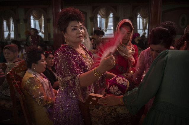 A Uyghur woman fans the mother of the groom after she was overcome at her son's wedding celebration on August 2, 2014 in Kashgar, Xinjiang Province, China. (Photo by Kevin Frayer/Getty Images)