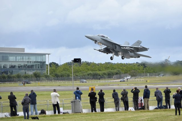 A Boeing F/A-18 takes off to perform during the Farnborough International Airshow in Farnborough, Britain, 12 July 2016. The Farnborough International Air Show runs from 11-17 July. (Photo by Hannah Mckay/EPA)